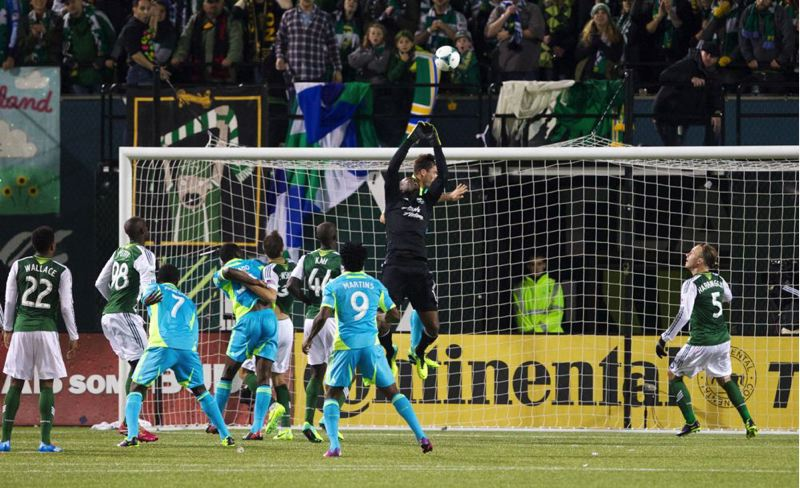 Portland goalie Donovan Ricketts punches a Seattle shot over the bar in the second half.