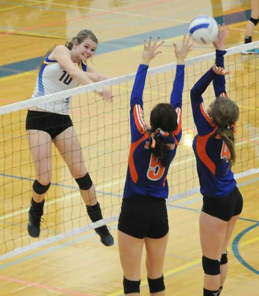 by: LON AUSTIN/CENTRAL OREGONIAN - Karlee Hollis blasts a kill through a pair of Hidden Valley blockers during Crook County's semifinal victory over the Mustangs.