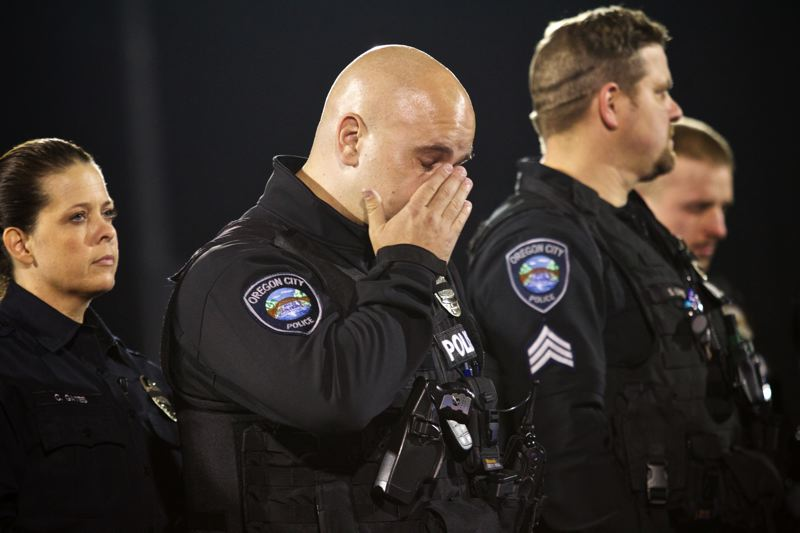 by: PHOTO BY: JAIME VALDEZ - Oregon City Police Officer Brian Willard wipes away a tear after balloons were released by fellow police officers for his friend, OCPD Reserve Officer Robert Libke.