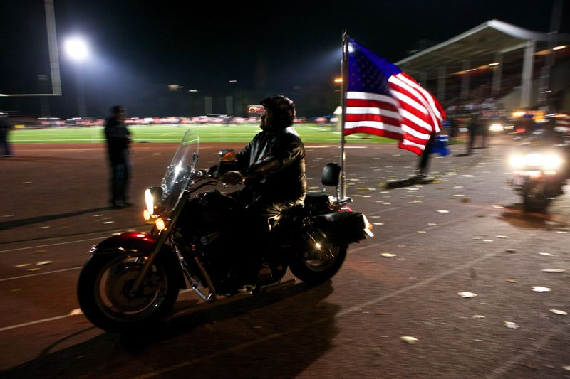 by: PHOTO BY: JAIME VALDEZ - Patriot Guard Riders lap the track at Pioneer Stadium before Friday's playoff game in honor of Officer Robert Libke.