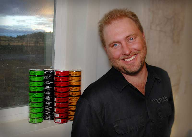 by: CONTRIBUTED PHOTO - Aaron Young stands in front of stacks of his four blends of all-natural herbal chew.