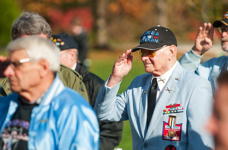 by: SPOKESMAN PHOTO: JOSH KULLA - Korean War veterans salute the flag during the playing of Taps Monday at a Veterans Day ceremony at the Oregon Korean War Memorial in Wilsonville.