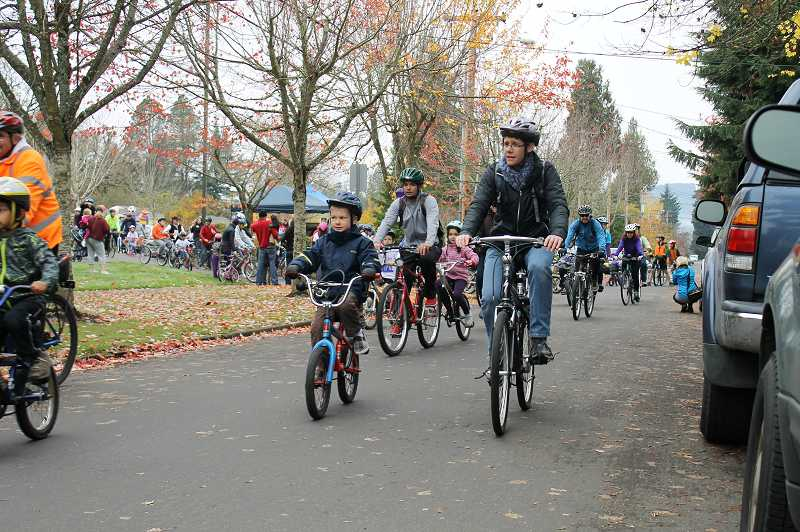 by: NEWS-TIMES PHOTO: JOHN SCHRAG - A throng of bicycle riders, including Nicki Butler and her son Evan (foreground), as well as Sam Marshall and his daughter McKenzie (center background), take off from behind the Forest Grove School District office on the four-mile Cycle of Life route Saturday. About 400 people showed up to the event honoring sisters Abigail Robinson and Anna Dieter-Eckerdt.