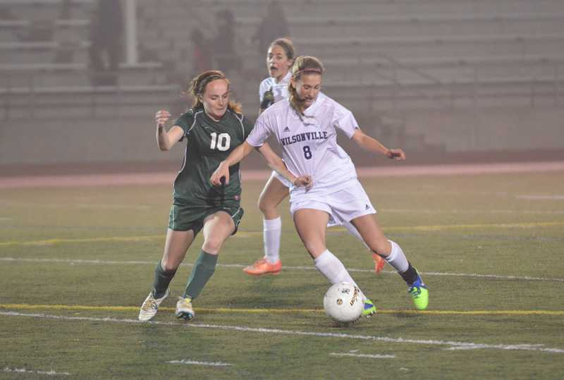 by: JEFF GOODMAN / PAMPLIN MEDIA GROUP - Wilson midfielder Mara McLaughlin (left) battles Wilsonville senior Savannah Stehman for possession in a Class 5A girls soccer semifinal Nov. 12. The Trojans advanced to the title match for the first time since 1977 with a win over the Wildcats.