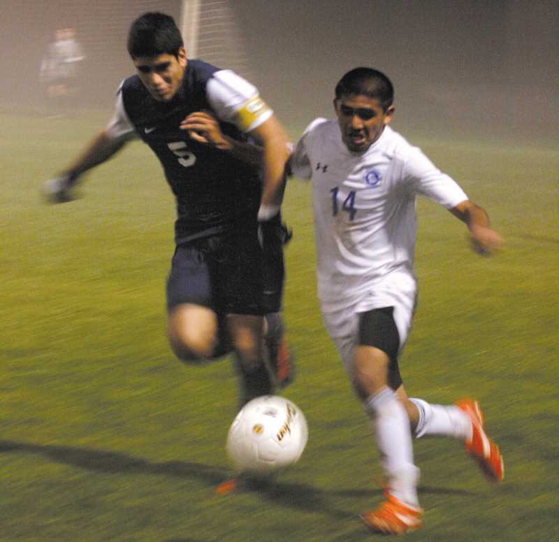 by: PHIL HAWKINS - Anthony Santillan fights for possession along the sideline in the first half of Tuesday's 5A semifinal game against the Hood River Valley Eagles.