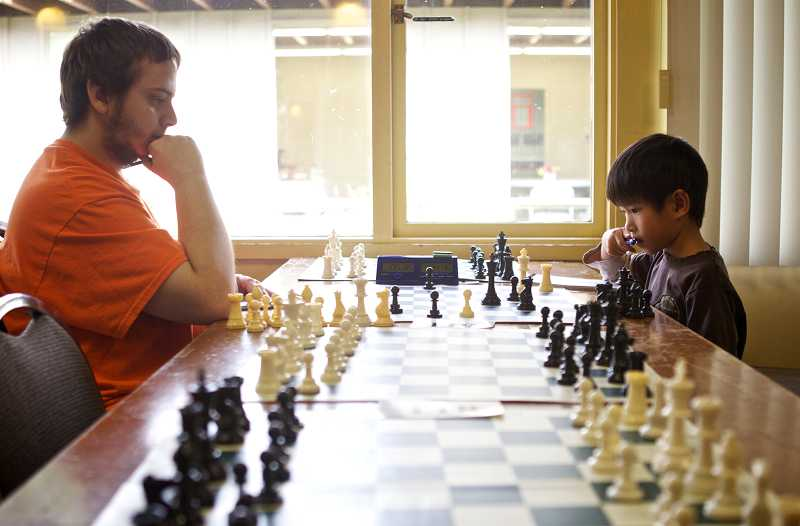 by: TIMES PHOTO:JAIME VALDEZ - Devon Gregory watches as Egan Wong ponders his next move during a chess tournament at the Bethlehem-House of Bread open house.