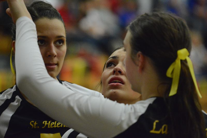 by: JOHN WILLIAM HOWARD - Logan Kalauli (center) searches for a way to cope seconds after St. Helens fell to Willamette in the opening round. She and teammates Gabby Susee (left) and Taylor Albertson have been part of one of the most dominant groups of hitters in school history.