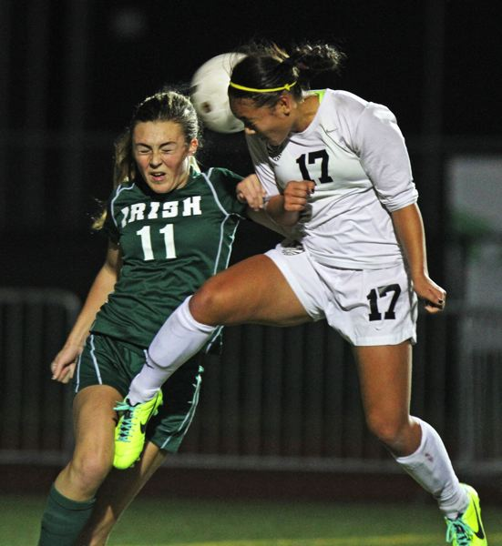 by: JONATHAN HOUSE - STAYING STRONG -- Tualatin sophomore Corinne Togiai (right) goes up above Sheldon's Mary Jane Ervingto get her head on the ball during Saturday's Class 6A state semifinal match. The Wolves won 1-0.