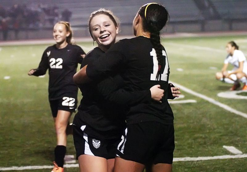 by: DAN BROOD - TO THE CHAMPIONSHIP -- Tualatin soph'more Kyla Hackelman hugs sophomore teammate Corinne Togiai (17) following the Wolves' 2-0 win over Jesuit in Tuesday's semifinal match.