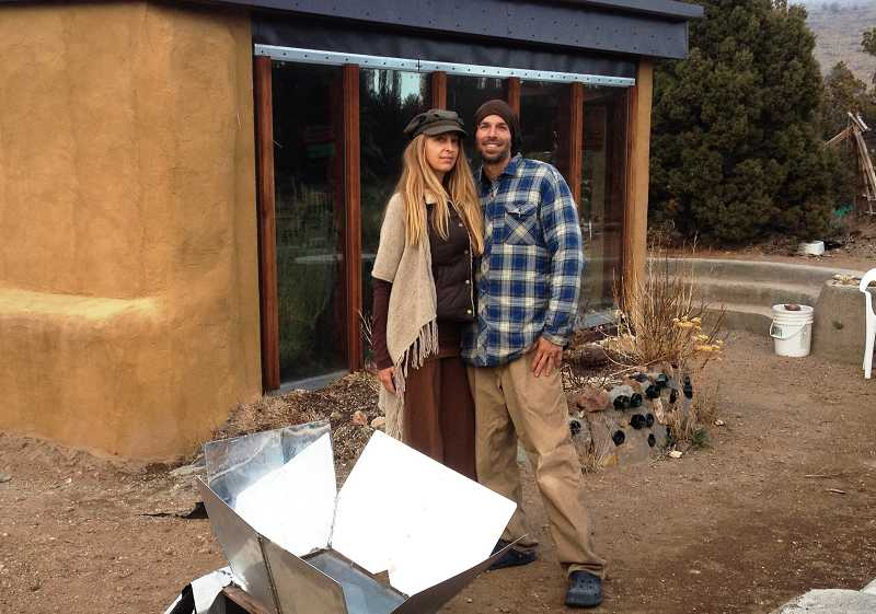 by: BILL MINTIENS - Linda and Patrick Oliver stand in front of their EcoPod that is powered by solar and wind energy.