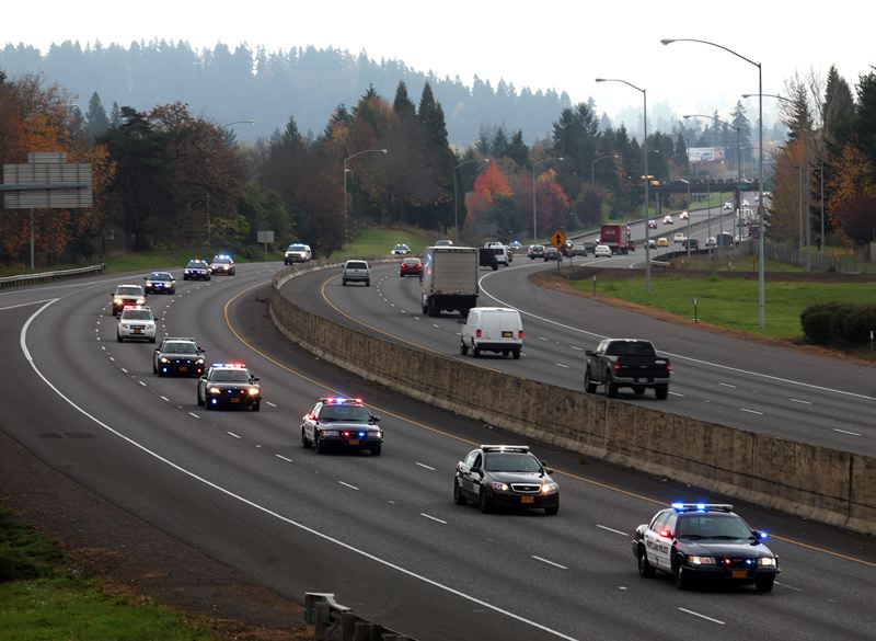 by: PAMPLIN MEDIA GROUP: JONATHAN HOUSE - Patrol cars from several law enforcement agencies led a procession on Interstate 205 prior to Thursday's memorial service in Portland for Oregon City Officer Robert Lipke.