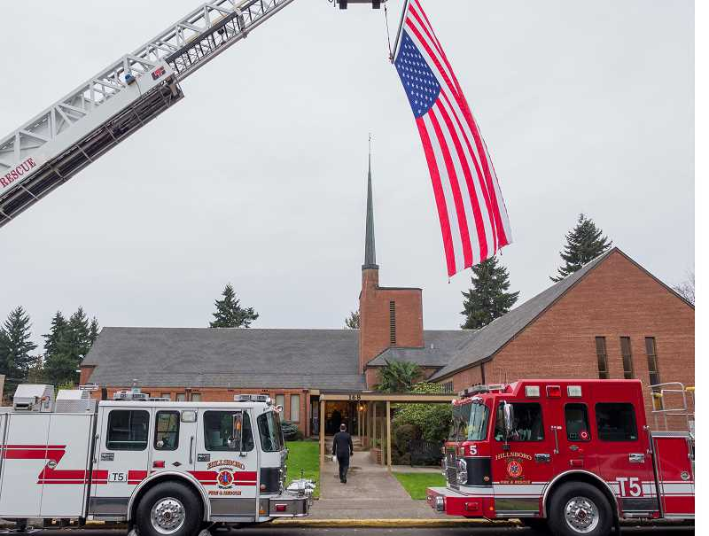 by: HILLSBORO TRIBUNE PHOTO: CHASE ALLGOOD - Friends and family of former Hillsboro Fire Chief Dayton Arruda gathered at Hillsboros United Methodist Church Saturday morning to honor Arrudas many years of service. Two ladder trucks marked the entrance to the memorial service with a large American flag flying in tribute.