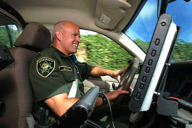 by: OUTLOOK FILE PHOTO: JIM CLARK - On duty, Graziano cruises in his patrol car through Corbett.