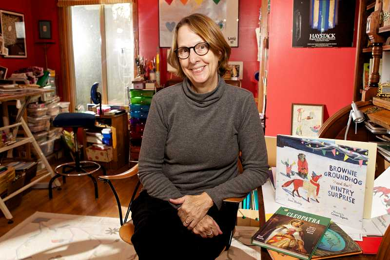 by: TIMES PHOTO: JAIME VALDEZ - Children's book author Susan Blackaby shows off copies of two of her books, her latest, 'Brownie Groundhog and the Wintry Surprise,' and 'Cleopatra' from 2009, in the workshop at her Raleigh Hills home. Blackaby will sign copies of her latest book on Saturday at Annie Bloom's Books in Multnomah Village.