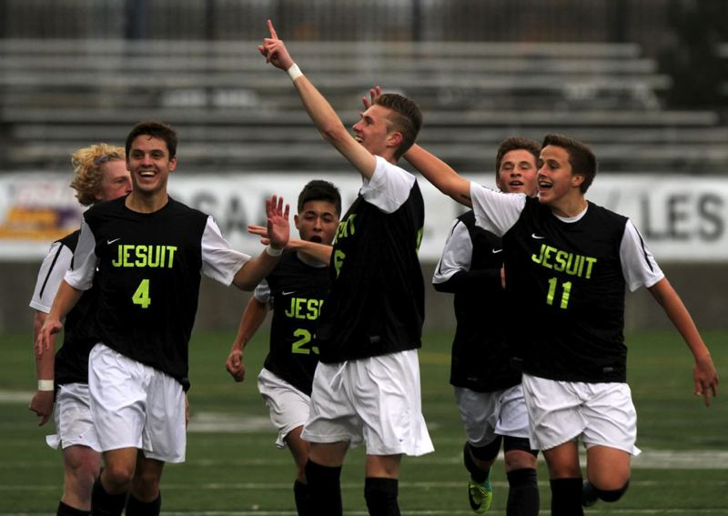 Jesuit teammates, including Spencer Scott (left) and Chase Boone (right), celebrate after the sixth-minute goal by Christopher Chertude (center) gives the Crusaders a 1-0 lead.
