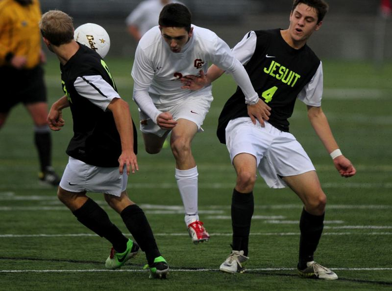 Central Catholic's Joseph Eli gets tripped up as he tries to split two Crusader defenders.