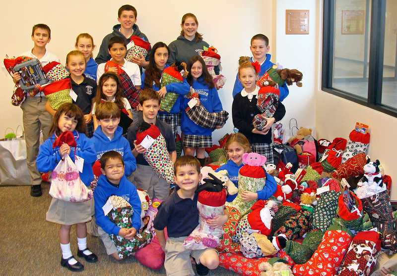 by: SUBMITTED PHOTO - The Our Lady of the Lake Catholic School community, in conjunction with the Our Lady of the Lake Parish, aims to stuff 300 stockings for Fill a Stocking, Fill a Heart. Students posed last year with their brimming stockings.