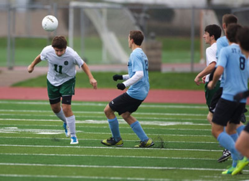 Nick Robinson, OES defender, heads the ball forward against St. Mary's.