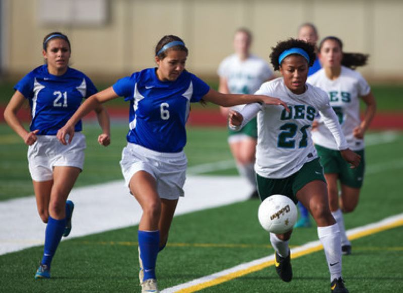 OES midfielder Mickaelah McKinney-Griggs (right) pushes the pace against Valley Catholic defendersMakenzee Cleveland (left) and Regan Torres.