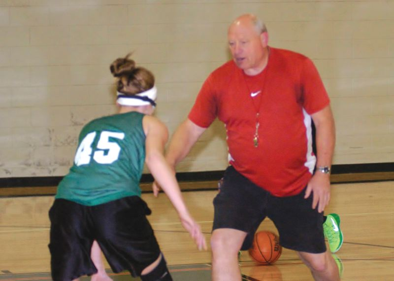 by: ESTACADA NEWS: PARKER LEE - New Estacada girls basketball coach Michael Pomerenke teaches a defensive drill during an early-season practice Monday.