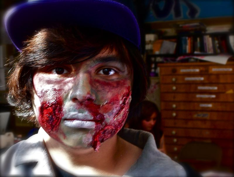 by: PHOTO BY: MARTIN WINCH - New Urban High School freshman Austin Brown portrays a zombie with makeup by Kat Synder.