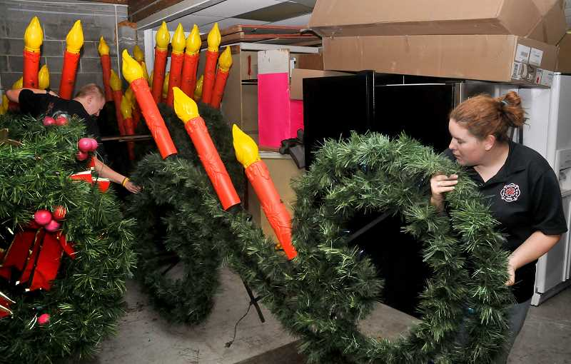 by: GARY ALLEN - Tradition - The Newberg Fire Department owns 69 scrolls, and 40 wreath decorations, plus lights to decorate trees located at the Newberg Public Library and at Highway 99W and Elliott Road. The scrolls are maintained by firefighters.