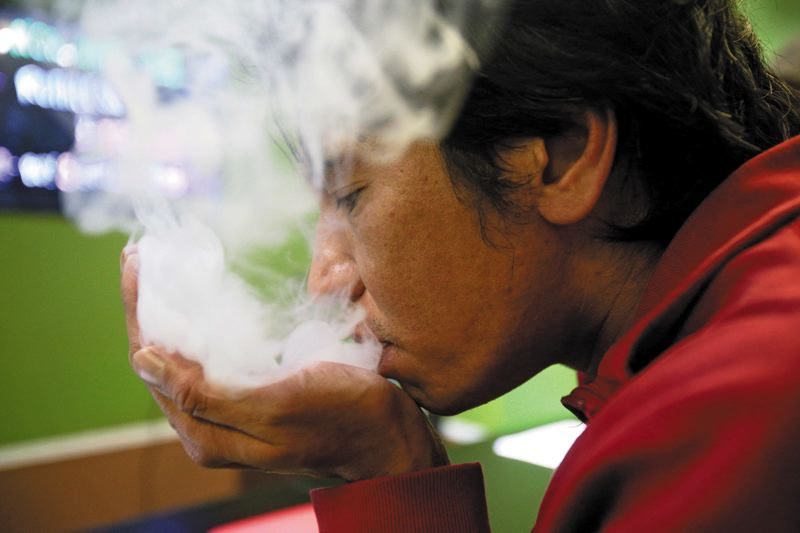 by: TRIBUNE PHOTO: JONATHAN HOUSE - Ben Arboleda blows a cloud of vapor into his hand after taking a puff from his electronic cigarette at Escape Vapor Lounge. E-cigs helped Arboleda quit smoking cigarettes.