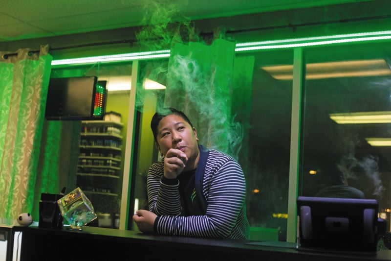 by: TRIBUNE PHOTO: JONATHAN HOUSE - Escape Vapor Lounges marketing manager Darlene Gorgonia takes a puff on her e-cig. Gorgonia, a former cigarette smoker, enjoys the hobby and culture of vaping as a safer alternative.