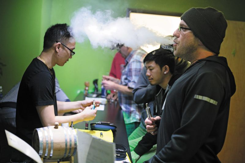 by: TRIBUNE PHOTO: JONATHAN HOUSE - Robert Lippert enjoys an e-cig at Escape Vapor Lounge while employee Sopon Muanprasitivej shows customers various e-cigs for sale.