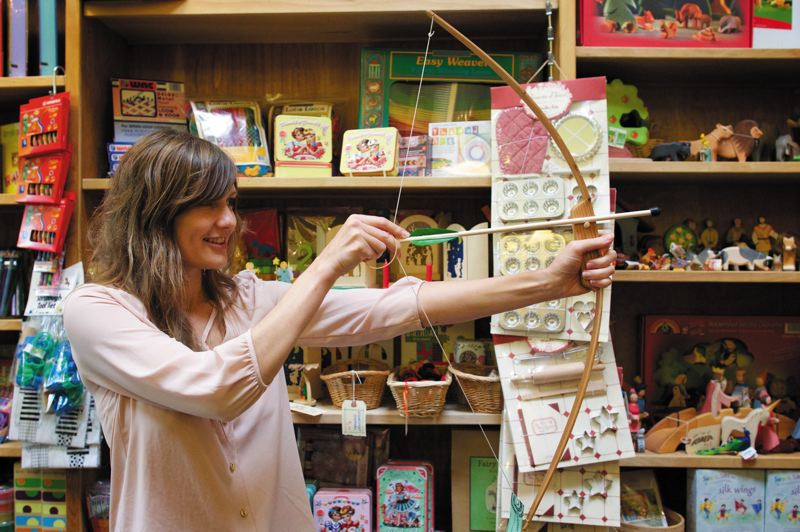by: TRIBUNE PHOTO: JAIME VALDEZ - SpielWerks Toys owner Stacee Wion shows off a quality-made bow and arrow set, made by Portland woodworker Brendan Budge. The North Williams shop and others participating in Little Boxes sell unique goods, many of them made locally and others procured from around the globe. Organizers hope for a big shop local turnout.