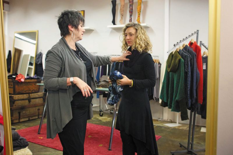 by: TRIBUNE PHOTO: JAIME VALDEZ  - Jeanna Andros Baker, shop manager at Jet Clothing on North Mississippi, helps Anna Reed try on the Barcelona dress. The clothes here are locally designed and sewn.
