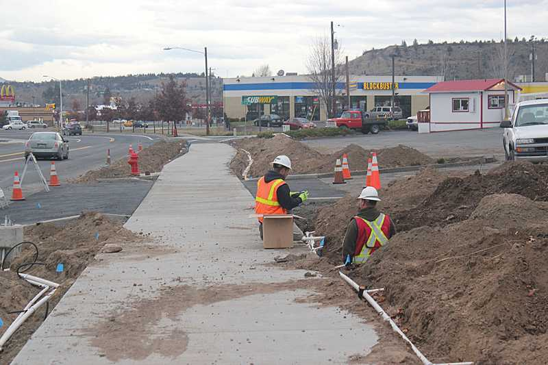 by: HOLLY M. GILL - Construction workers from R-2 Construction install a hookup for irrigation lines along a new sidewalk that stretches from Plum Street to Cedar Street, just east of the Les Schwab Tire Center.