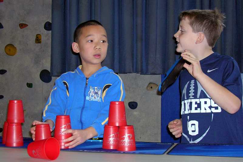 by: REVIEW PHOTO: JILLIAN DALEY - Lake Grove third-grader Blake Hilliker shows a fellow cup stacker, third-grader Albert Yan, his time.