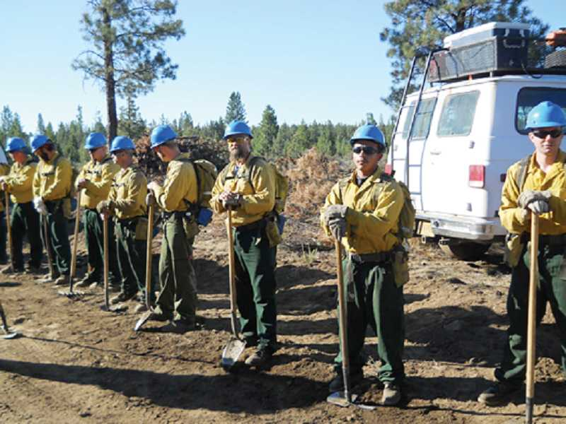 by: SUBMITTED PHOTO - Inmates from DRCI pose for a photo at one of the four fires they fought last summer.