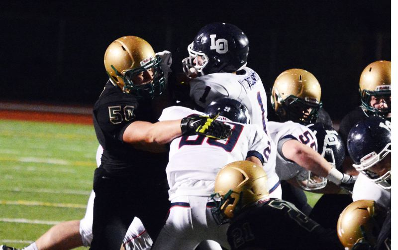 by: TIMES PHOTO: MATT SINGLEDECKER - Jesuit junior defensive tackle Nick Miller fights about a Lake Oswego pass block in the first quarter of the Crusaders 21-19 over the Lakers on Friday.