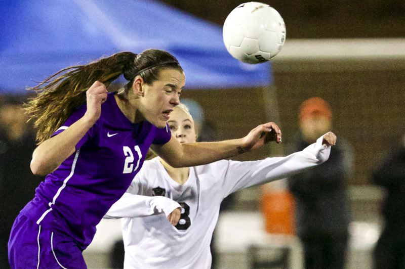 by: TIMES PHOTO: JAIME VALDEZ - Sunset Apollos defender Taylor Coon (21) heads the ball over Tualatin Timberwolves Jordan Anderson (8 )in the  6A state girls soccer championship at Hillsboro Stadium.