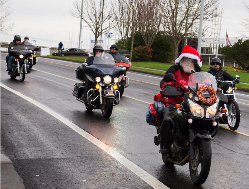 by: HILLSBORO TRIBUNE PHOTOS: CHASE ALLGOOD - Rich Verchow, leading the way as this years honorary Santa Claus, offers a friendly wave as motorcyclists roll out to escort a truckload of toys going to the Elks Lodge.