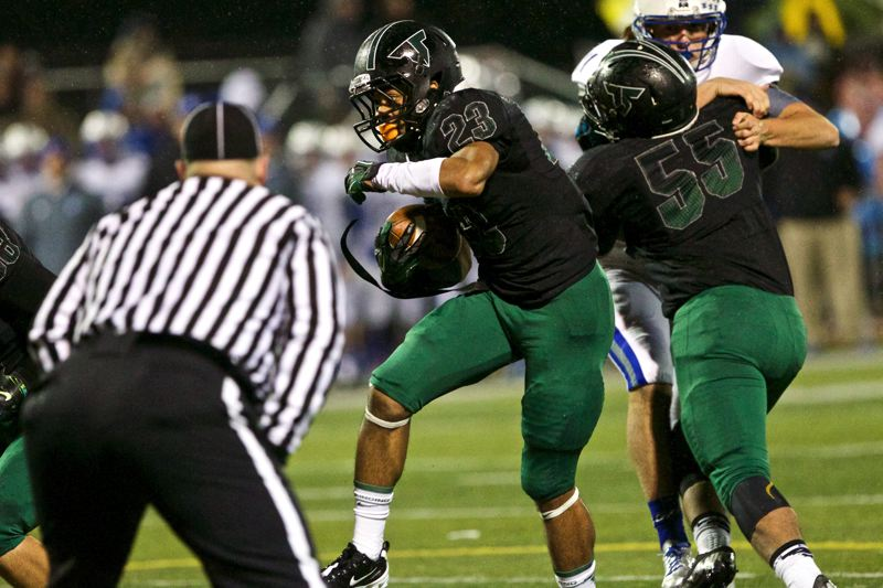 by: JAIME VALDEZ - RUNNING STRONG -- Tigard junior Landon Floyd (23) picks up yards behind a big block by Tigard senior lineman Byron Hammick Jr.