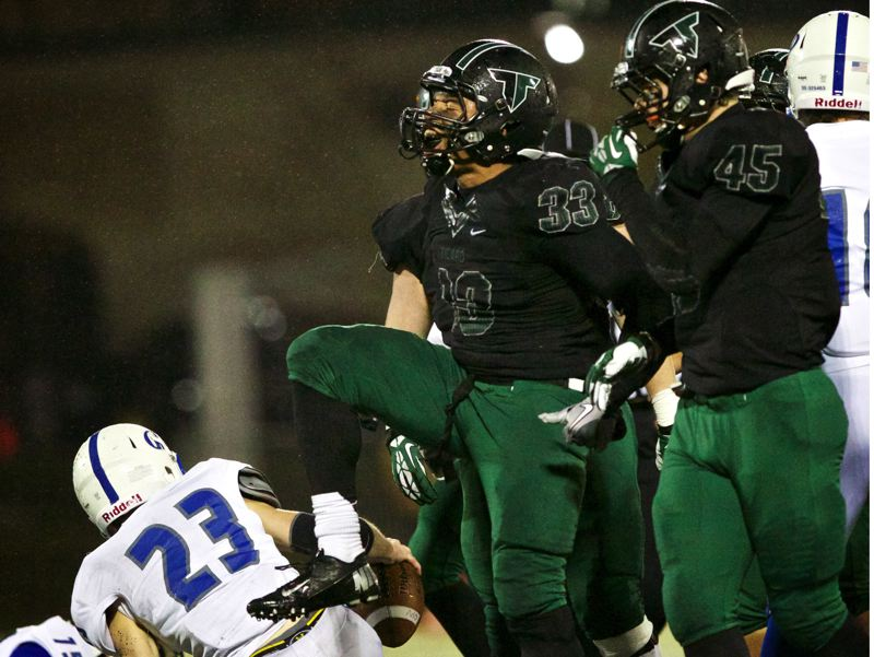 by: JAIME VALDEZ - Tigard senior linebacker AJ Hotchkins (33), next to teammate Joe Lobbato, yells after tackling Grants Pass  running back Zachary Hannan (23) in the first half of the second-round playoff game.