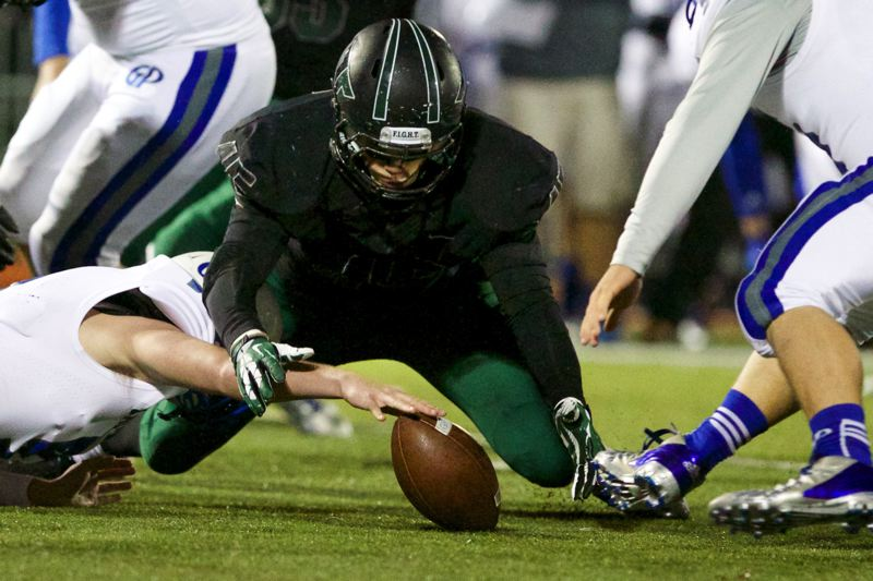 by: JAIME VALDEZ - Tigard senior defensive lineman Joe Lobbato (45) pounces on the ball after Grants Pass Cavemen quarterback Javan Appling fumbled on the opening possession of last Friday's state playoff game.