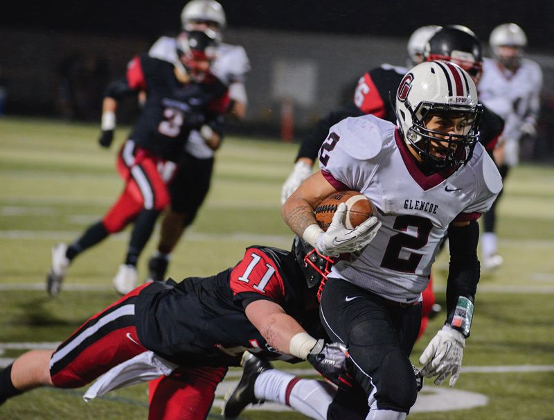 by: HILLSBORO TRIBUNE PHOTO: CHASE ALLGOOD - Glencoe running back Anthony Lambert runs through the attempted tackle of Clackamas linebacker Zach Farnes during last Friday's second-round Class 6A state playoff game.