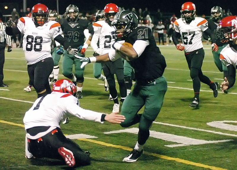 by: DAN BROOD - TO THE HOUSE -- Tigard junior Sam Inos avoids North Medford senior Micah Brown on his way to scoring on a 17-yard run in the Tigers' quarterfinal win.