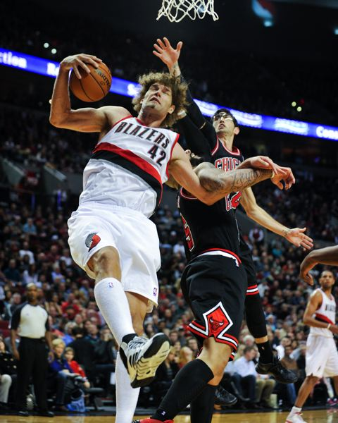 Robin Lopez hauls in one of his game-high 16 rebounds, beating Carlos Boozer and Kirk Hinrich to the ball.