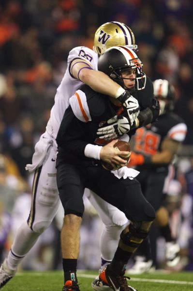 Beavers QB Sean Mannion is wrapped up by Washington defensive end Evan Hudson in the second half at Reser Stadium.
