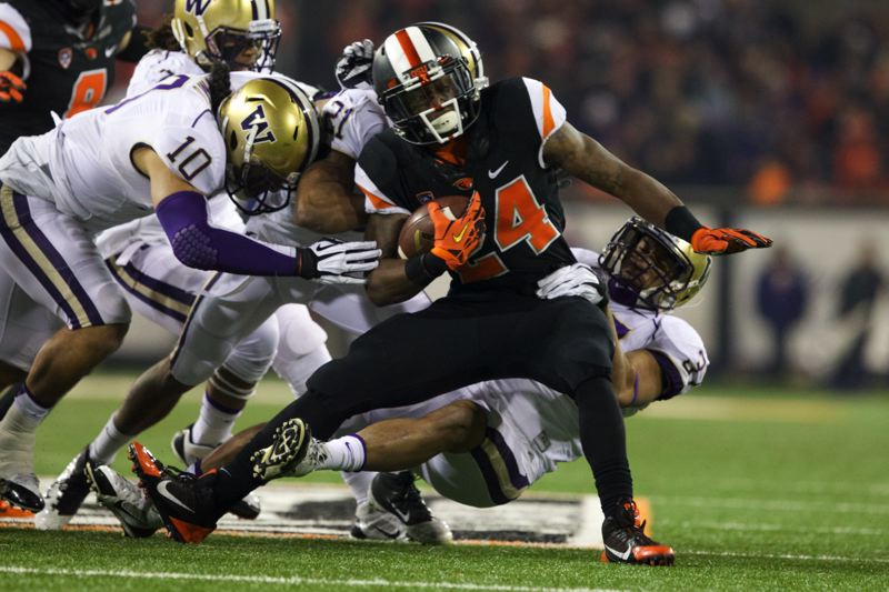 OSU running back Storm Woods is gobbled up by Washington's John Tims (left), Marcus Peters (21) and Princeton Tuimaono in the first half.