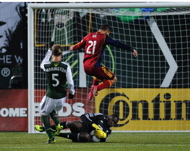 Portland keeper Donovan Ricketts slides and gets the ball just before the arrival of Luis Gil of RSL, as Timbers defender Michael Harrington gives chase.