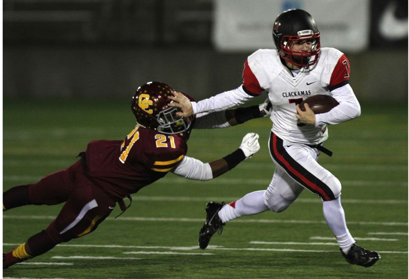 by: JON HOUSE - Clackamas senior running back Dan Sherrell repels Central Catholic senior defensive back Aaron Washington (21) in the Cavaliers quarterfinal game with the Rams. Sherrell had an incredible senior year, rushing for a school-record 2,266 yards and scoring a school-record 33 touchdowns.