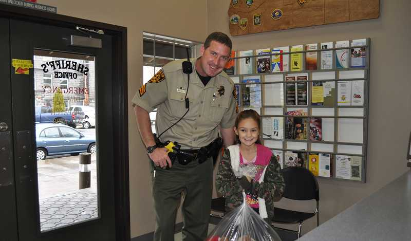 by: CONTRIBUTED PHOTO - Prineville 10-year-old Ivy Cater drops off a bag of stuffed animals she collected at the Crook County Sheriff's Office to the pleasant surprise of Sergeant James Savage.