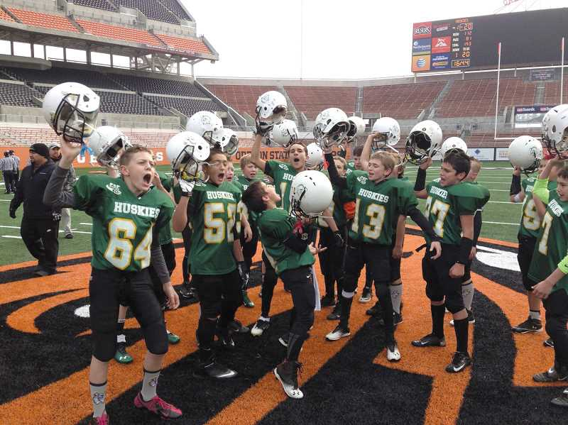 by: JASON COUSINS - The North Marion Husky Pee Wee football team celebrates at the 50-yard line in Oregon State Universitys Reser Stadium after winning the Alumni Bowl on Nov. 17.