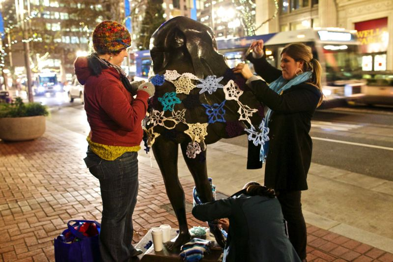 by: TRIBUNE PHOTO: JAIME VALDEZ - Jessica DeVries, Jenny Mosher and Claudia Martinez (crouching below) yarn-bomb the Kvinneakt statue downtown last week, part of the downtown retail strategys campaign this holiday season. Temporary pop-up stores have drawn shoppers downtown since 2009, but this year theyre on hiatus.
